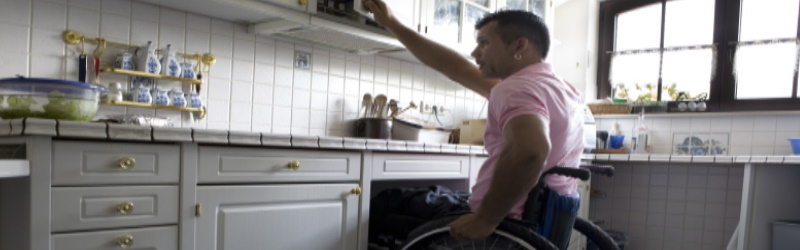 man in wheelchair opening upper cabinet door in kitchen