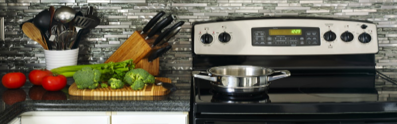 countertop with fresh vegetables, knife block, and container of kitchen utensils next to electric stovetop