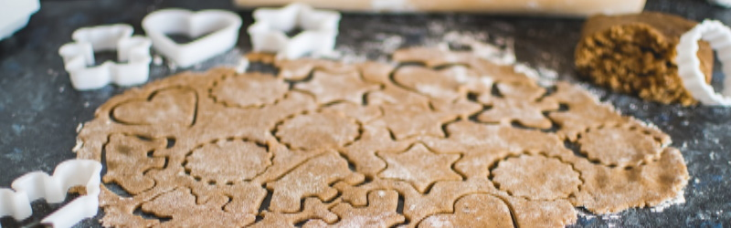 gingerbread cookie dough rolled out with cookie cutter shapes in dough