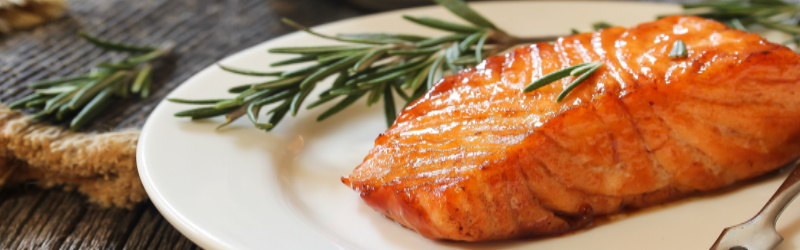 piece of cooked salmon on white plate next to sprig of rosemary