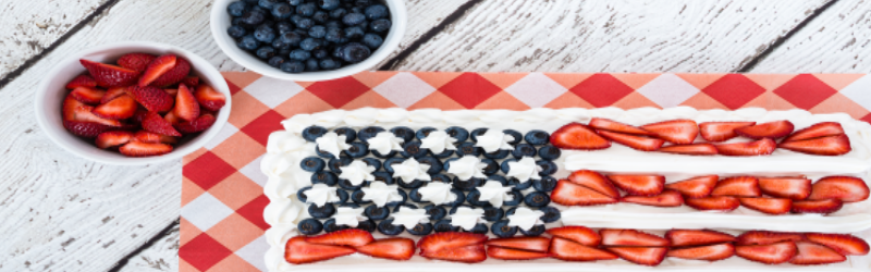 decorated American flag cake using blueberries, sliced strawberries, and white icing; bowls of sliced strawberries and blueberries in top left corner