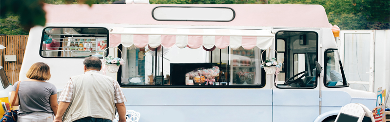 couple walking up to a white and pink food truck