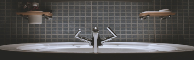 bathroom sink and faucet with tiled wall