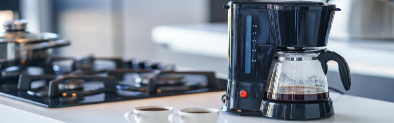 coffee maker on countertop next to gas stovetop with two cups of coffee