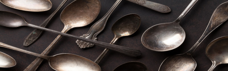 tarnished spoons of varying sizes and shapes on dark background