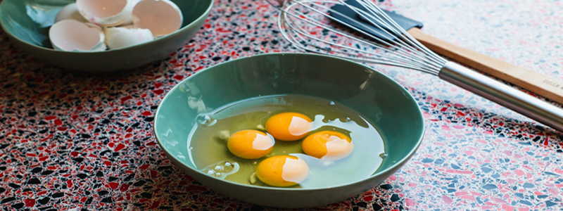four cracked eggs in green bowl with bowl of cracked eggshells and whisk in background