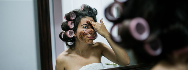 woman with curlers in her hair looking into a mirror and applying coffee ground exfoliant to face
